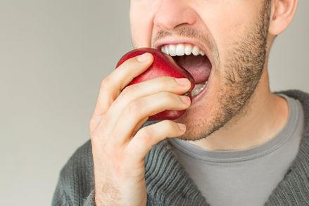 a man biting an apple